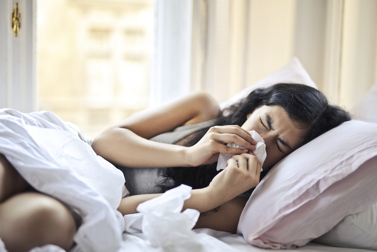 bed woman sneezing